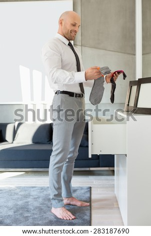 Full length side view of businessman selecting socks at home