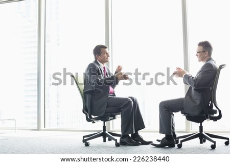 Full-length side view of businessmen discussing while sitting on office chairs by window - stock photo