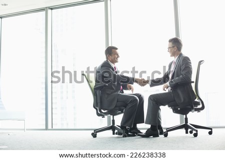 Full-length side view of businessmen shaking hands while sitting on office chairs by window - stock photo