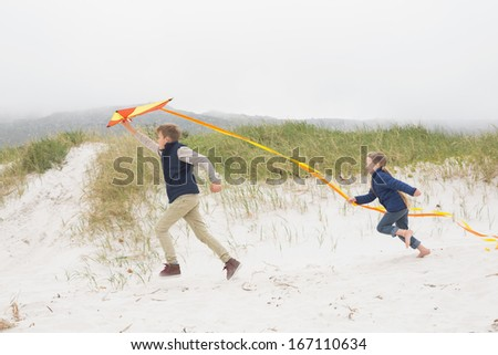 Full length side view of cheerful kids running with kite at the beach - stock photo
