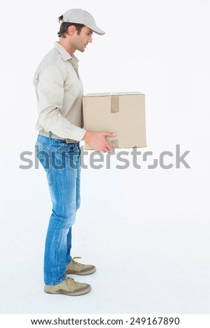 Full length side view of delivery man carrying cardboard box against white background