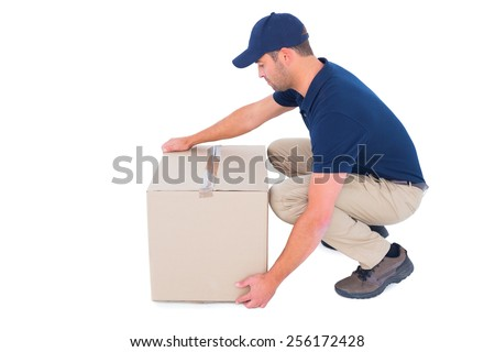 Full length side view of delivery man crouching while picking cardboard box on white background - stock photo