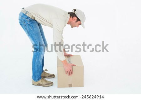 Full length side view of delivery man picking cardboard box against white background - stock photo