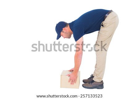 Full length side view of delivery man picking cardboard box on white background