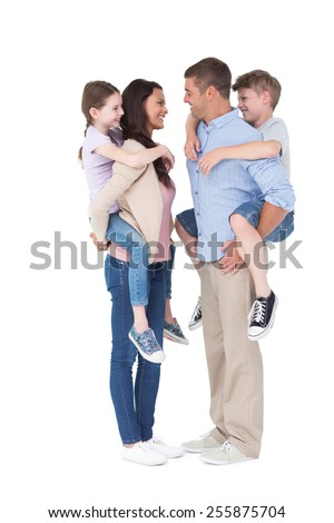 Full length side view of happy parents giving piggyback ride to children over white background - stock photo