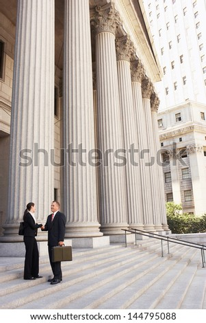 Full length side view of male and female attorneys shaking hands on courthouse steps - stock photo