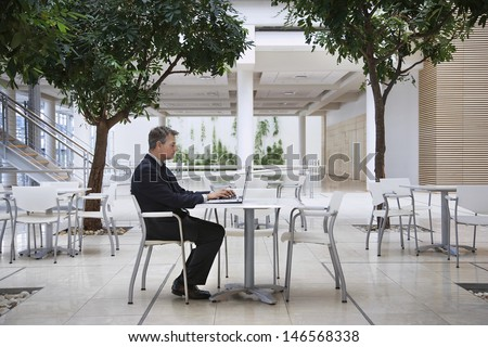Full length side view of middle aged businessman using laptop at office cafe