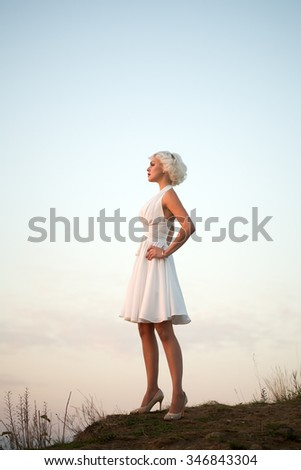 Full length side view of one young beautiful fashionable retro sexy woman with blonde hair in white dress standing outdoor in sunset on sky natural background, vertical picture - stock photo