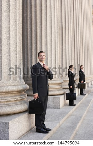 Full length side view of three attorneys waiting on courthouse steps - stock photo