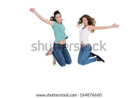 Full length side view of two cheerful young female friends jumping over white background