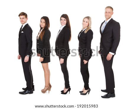 Full length side view of welldressed businesspeople standing in a line over white background