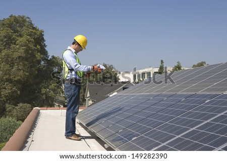 Full length side view of young maintenance worker inspecting solar panels on rooftop - stock photo