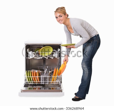 Full length side view of young woman arranging utensils in dishwasher over white background - stock photo