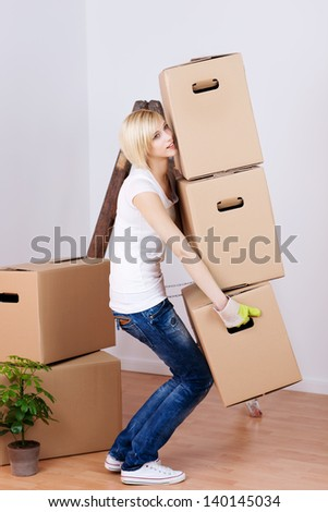 Full length side view of young woman carrying heavy cardboard boxes in house - stock photo