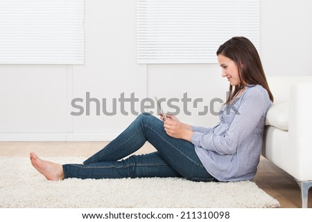Full length side view of young woman using tablet PC while sitting on rug at home - stock photo
