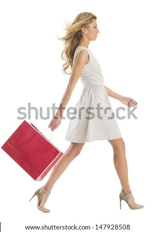 Full length side view of young woman walking with shopping bag isolated over white background - stock photo
