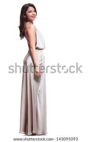 full length side view photo of a young beauty woman looking at the camera with a smile on her face. isolated on white background