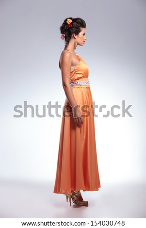 full length side view photo of a young fashion woman looking forward, away from the camera. on gray background