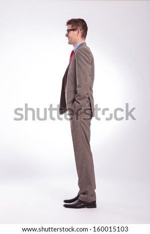 full length side view picture of a young business man with hands in pockets. on a gray background