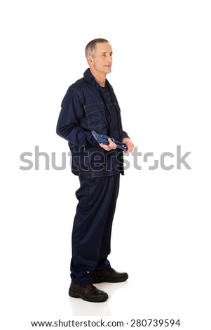 Full length side view plumber holding a wrench. - stock photo