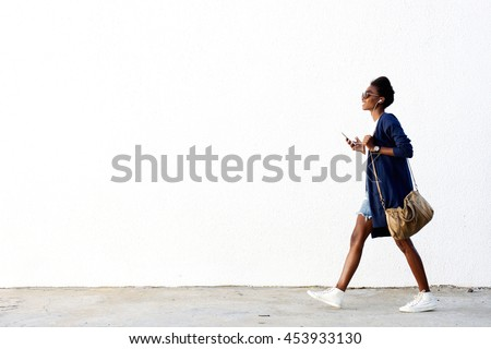 Full length side view portrait of trendy young black woman walking outdoors and listening to music on her mobile phone