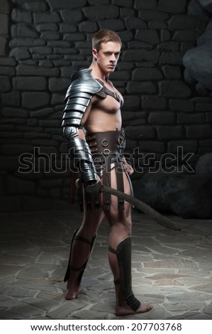 Full length side view portrait of young attractive warrior gladiator with muscular body posing with sword on dark background. Concept of masculine power, strength - stock photo