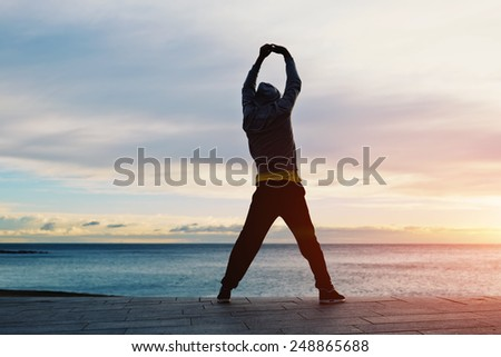 Full length silhouette portrait of a young jogger stretching in the morning and admiring beautiful view while standing on the beach - stock photo