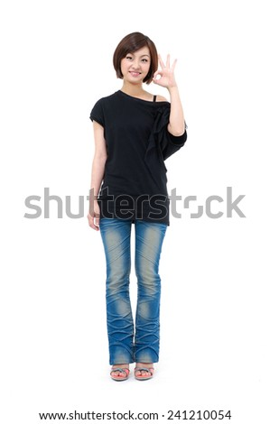Full length smiling asian posing show ok gesture in studio - stock photo