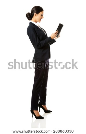 Full length smiling businesswoman reading her notes. - stock photo