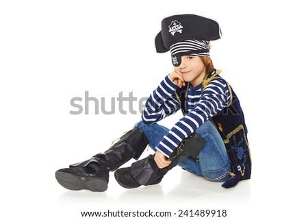 Full length smiling little boy wearing pirate costume sitting on the white studio floor, over white background - stock photo