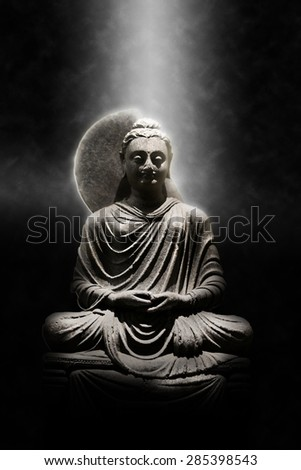 Full Length Stone Carved Seated Buddha Statue Dramatically Lit From Above On Dark Background Meditation