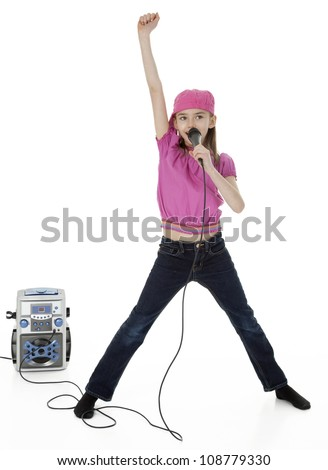 Full length studio photo of young girl holding microphone in front of karaoke machine, on white background.