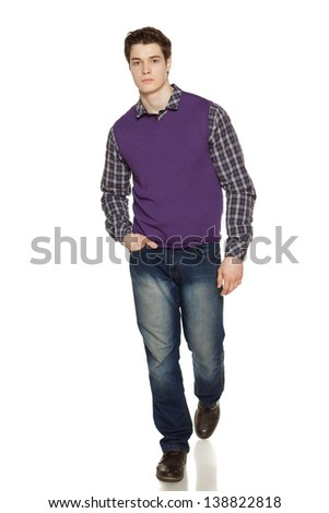 Full length studio portrait of a stylishly-dressed young man walking over white background - stock photo