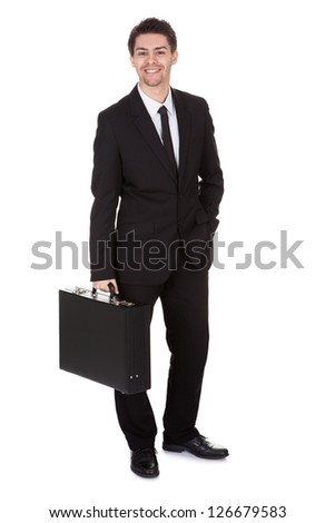Full length studio portrait on white of a smiling confident young businessman standing with suitcase