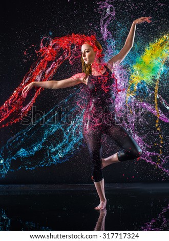 Full Length Studio Shot of Elegant Young Dancer Being Splashed with Colorful Water - Young Red Haired Woman in Ballet Pose in Black Studio