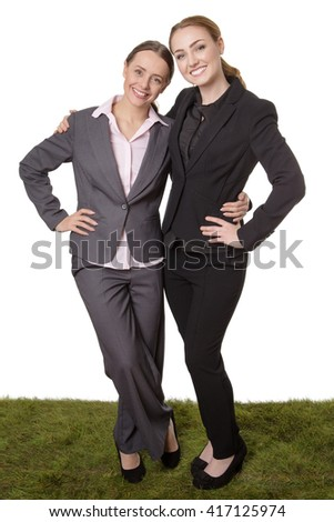 Full length Studio shot of two business models, standing on grass, laughing and joking together.  Enjoying a gossip. isolated on white background