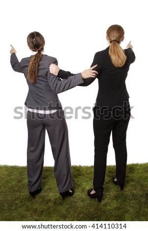 Full length studio shot of two business women, taken from behind, standing on grass. wanting to go in different directions - stock photo