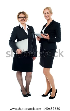 Full length studio shot of two businesswomen posing. - stock photo
