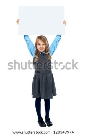 Full length studio shot smiling schoolgirl holding blank billboard above her head. - stock photo