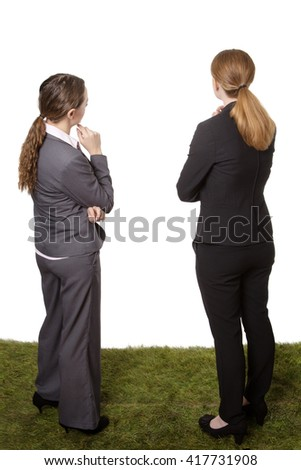 Full length studio shot taken from behind of two business models, standing on grass, looking thoughtful. Isolated on a white background.