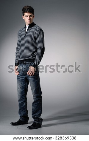 full length Stylish young man in jeans posing on light background - stock photo