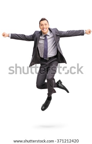 Full length vertical shot of a joyful businessman jumping out of happiness shot in mid-air isolated on white background - stock photo