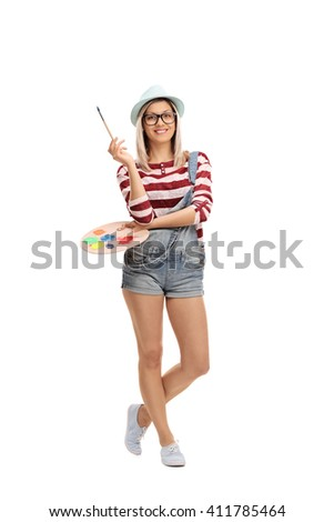 Full length vertical shot of a young beautiful woman holding a paintbrush and a color palette isolated on white background - stock photo