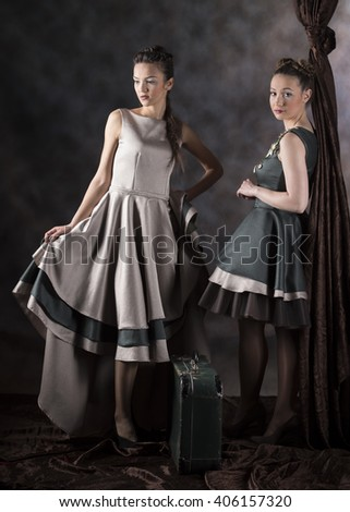 full length vertical studio image of two fashion models wearing gray and green layered designer dresses standing with a suitcase next to brown drapery and a gray background - stock photo