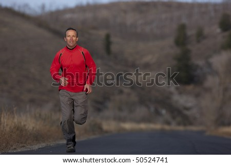 Full length view of a man running toward the camera on a country road. Horizontal format. - stock photo