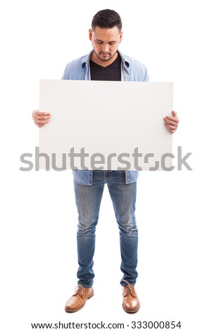 Full length view of a young Hispanic man dressed casually and holding a big sign against a white background - stock photo