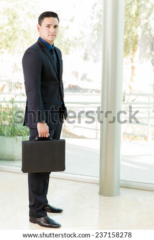 Full length view of a young Latin businessman carrying a briefcase - stock photo