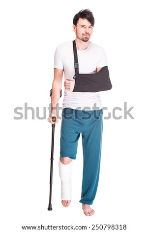 Full length view of a young man with broken leg and hand is using crutch isolated on white background. - stock photo