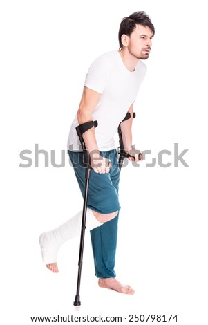 Full length view of a young man with broken leg is using crutch isolated on white background. - stock photo