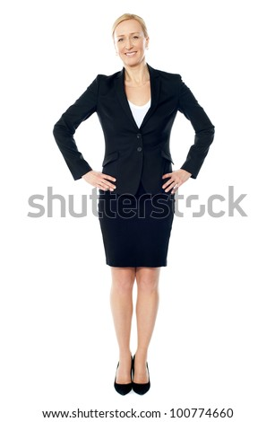 Full length view of attractive business executive posing with arms on her waist - stock photo